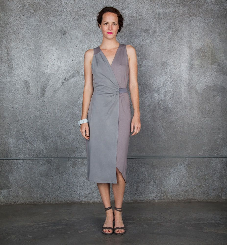 Bi-colored sleeveless Laura panel dress in muted greyand purple with gathered, belted waist and wraparound look.