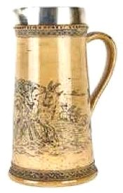 A large and early Royal Doulton Lambeth jug by Hannah Barlow (act.1871 - 1913), decorated sgraffito to the buff ground with a herd of ten goats in an extensive rural landscape, tapering cylindrical shape, the handle and the body adjoining the handle decorated with incised and coloured glazed trefoil leaves. With sterling silver rim, hallmarked London 1874. Height 270cm. (3.5K)
