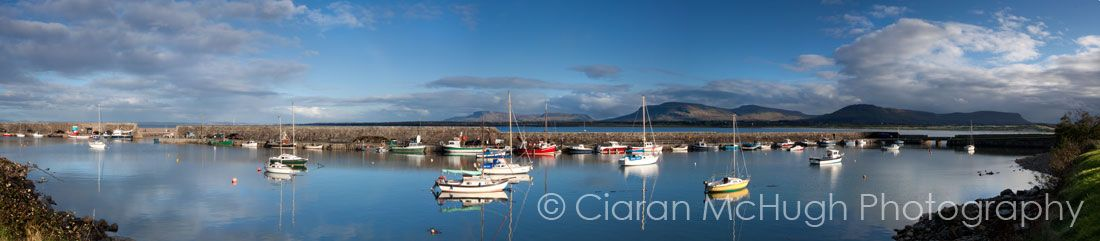 """""""Mullaghmore Harbour"""" -  Mullaghmore is a small but busy fishing village in North Sligo.  Much of the horizon at Mullaghmore is dominated by the striking Dartry Mountain range. In this photo these mountains are lit by a scattering of evening sunlight and the iconic outline of Benbulben can be seen in the far right of the picture, its northern face silhouetted against the sky. See more on http://www.ciaranmchugh.com/?pagid=mullaghmore-harbour"""