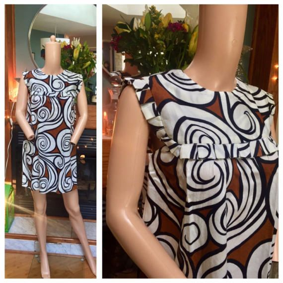 """About this dress:   - appears to be sewn by hand which is why it has no tags  - classic 60s shift dress  - zipper back with a vintage metal zipper  - ruffled details along the bodice and sleeveless armholes  - """"groovy"""" chocolate brown and off white print with black outlines"""
