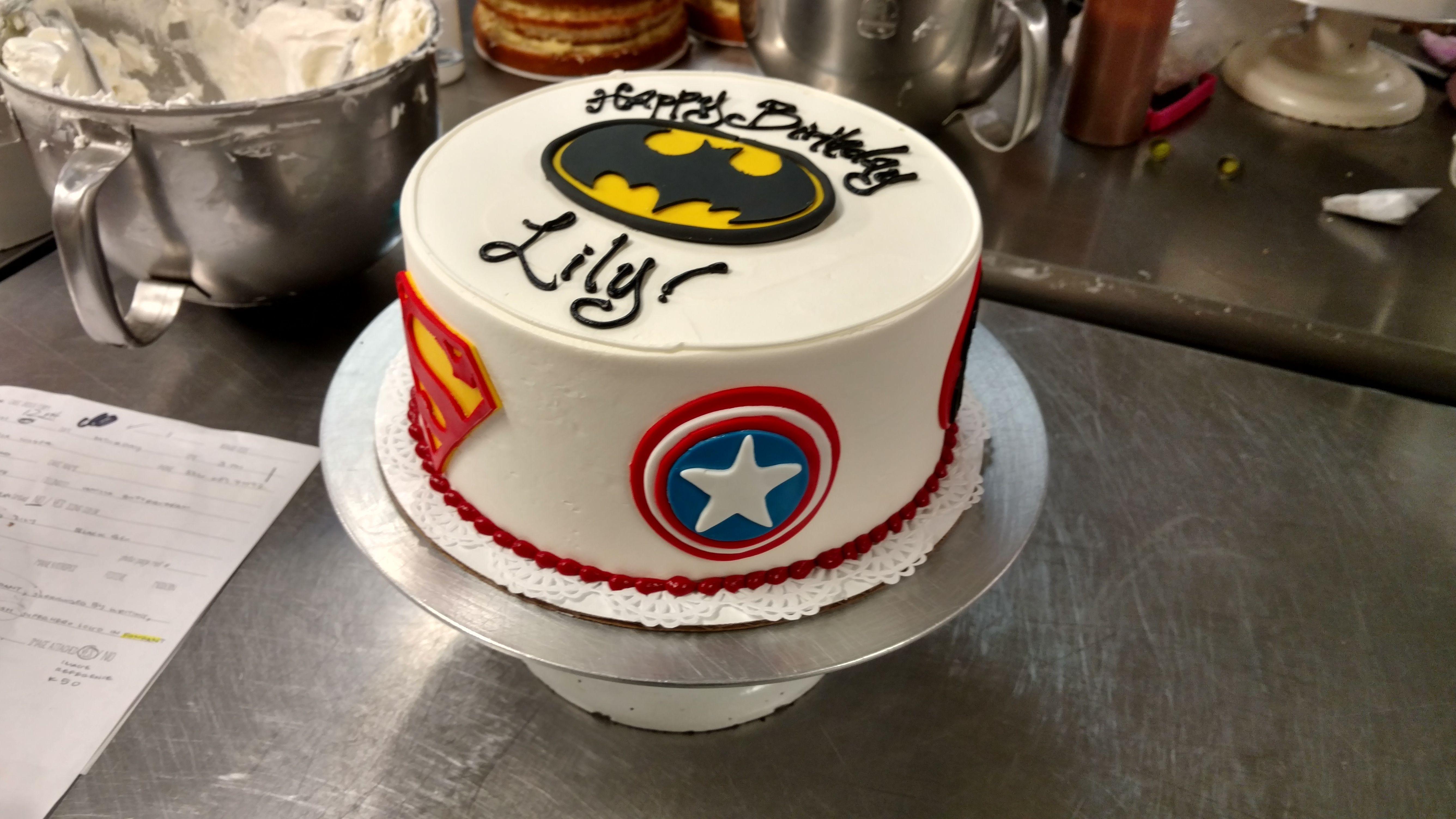 A Superhero Themed Birthday Cake With Fondant Dc And Marvel Logos