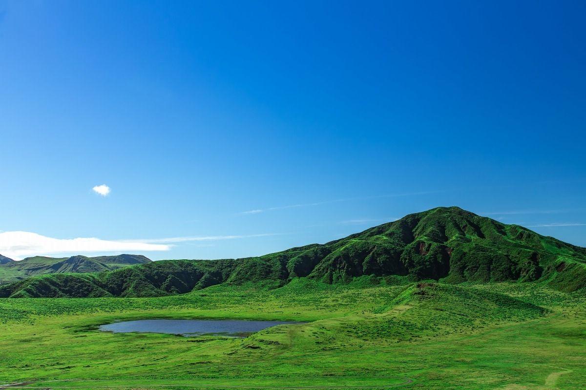 煙を上げる阿蘇山の中岳を望む、絶好のロケーションの草千里。直徑1キロメートルの広大な大草原の中央に ...