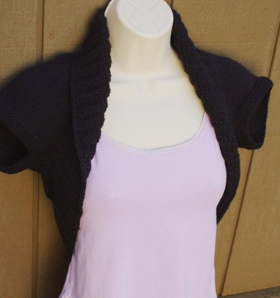 """This Black Licorice Knit Shrug vest will go great with your wardrobe. The arm holes are knitted in a garter stitch, while the trim is done in a 4"""" moss ribbed stitch, to hug the neck and body. This soft vest is knit in a light weight yarn, which makes it a year round accessory. This item makes a great gift or a lovely addition for yourself.  Medium fits size 36"""" to 38"""" Bust Generally fits size 8 to 10  This is a great item for tweens, teens and adults. There is no seam down the back, plus…"""