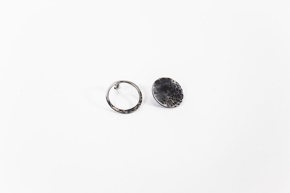 Textured moon and eclipse stud earrings, in partially oxidised sterling  silver.  Moon is a solid circle with light texturing.  Eclipse is a partially textured hollow ring.  Available as a matching pair of Moons or Eclipses, or a mismatched pair  withone of each.  Circles measure 1.8cm in diameter.
