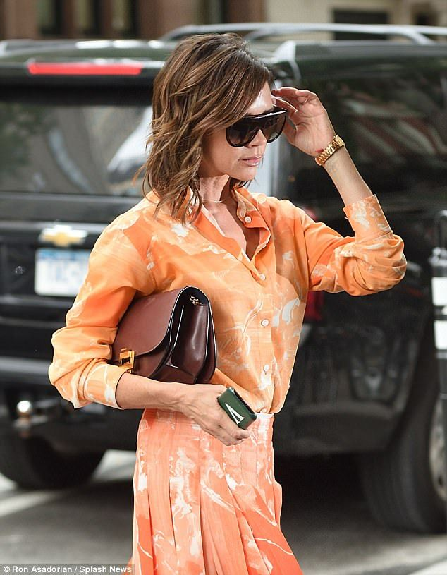 Chic: The fashionista carried a burgundy bag under one arm and flashed a look at her monogrammed phone case