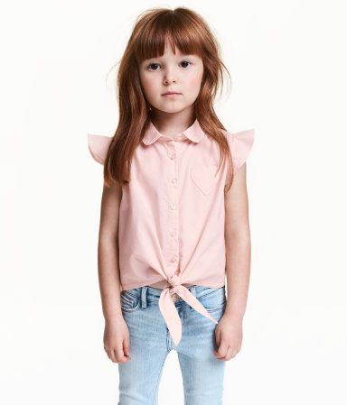 Light pink. Blouse in airy, woven cotton fabric with short ruffled sleeves, rounded collar, and buttons at front. Heart-shaped chest pocket, gathered yoke,
