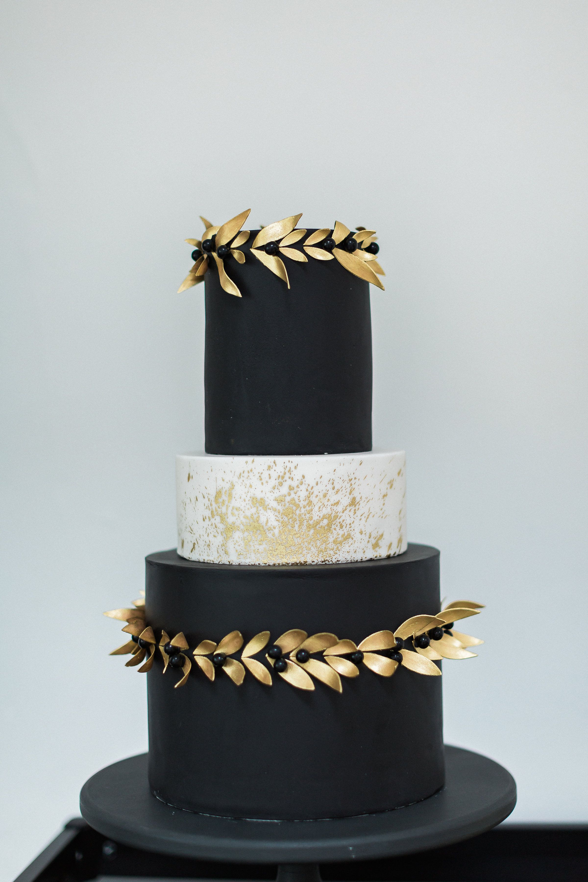 Black and white wedding cake with gold leaf garlands and gold ...