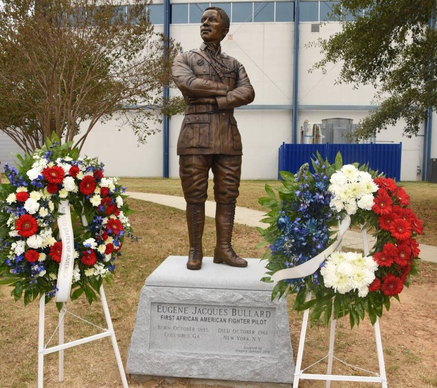 Two wreaths stand beside a statue of 2nd Lt. Eugene
