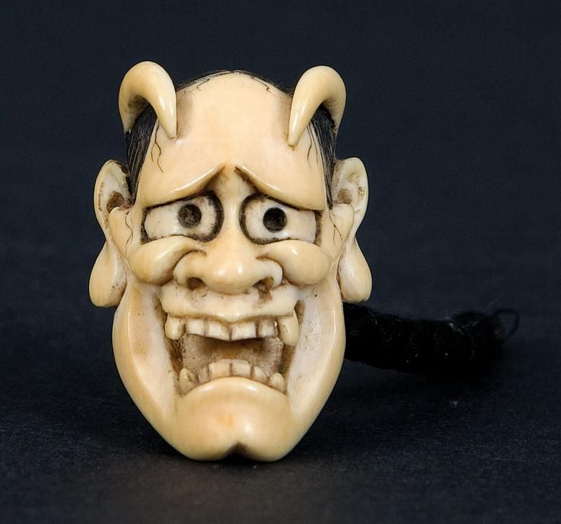 An ivory netsuke. 19th century, signed Koichi. A very finely carved and good small Noh mask of the female demon Hannya. Carved horns and grimacing open mouth with fangs. Has an attached silk cord, signed Koichi. Old English collection. Length 3.3 cm