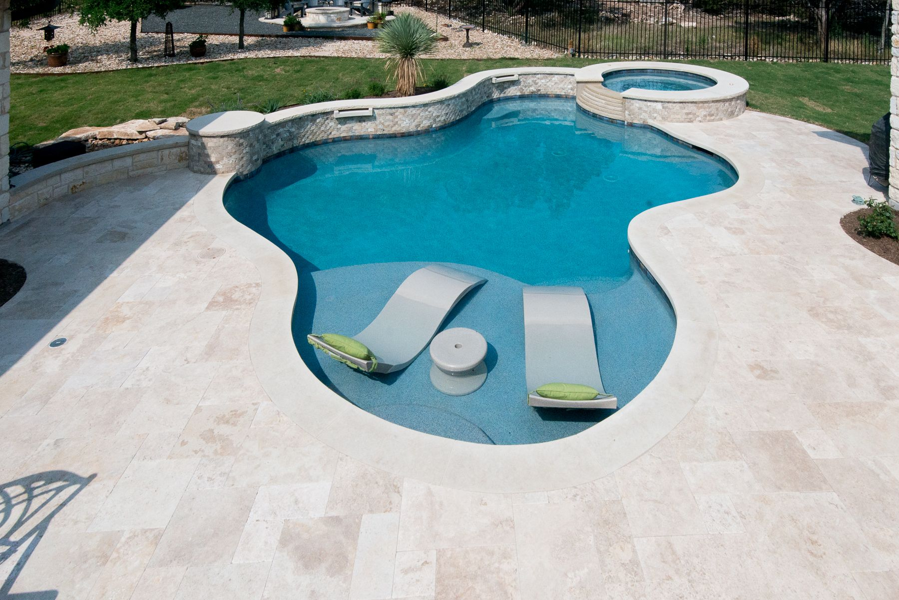 Travertine Deck With Lueder Coping Surrounding A Freeform Pool