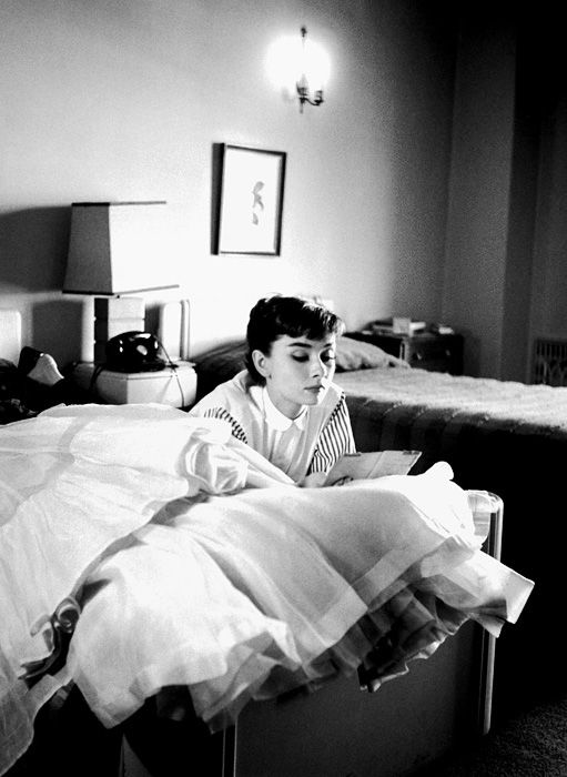 A 24 year old Audrey Hepburn exhausted from a long day at Paramount Studios, lays down in her Los Angeles hotel room reading a letter from home.  Photograph by Bob Willoughby (1953).