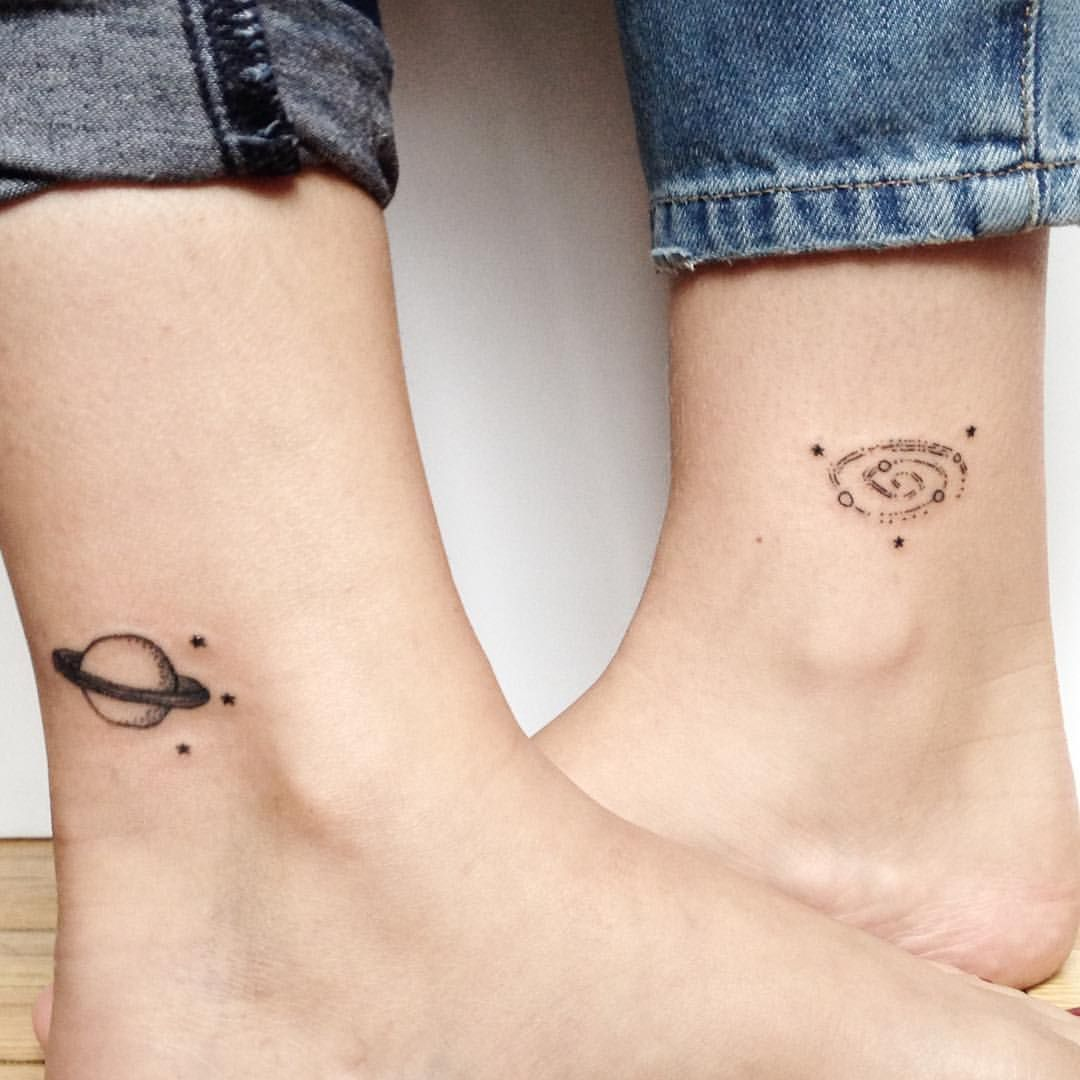 Matching Saturn And Spiral Galaxy Tattoos On The Ankles