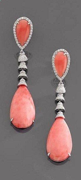 Paire de pendants doreilles corail Ils portent un cabochon piriforme de corail retenu par une suite de clochettes pavées de petits diamants taille brillant. Monture en or gris 18K