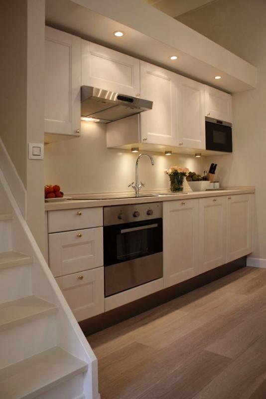 Cucina completamente attrezzata con armadi in legno sbiancati per complementare il parquet