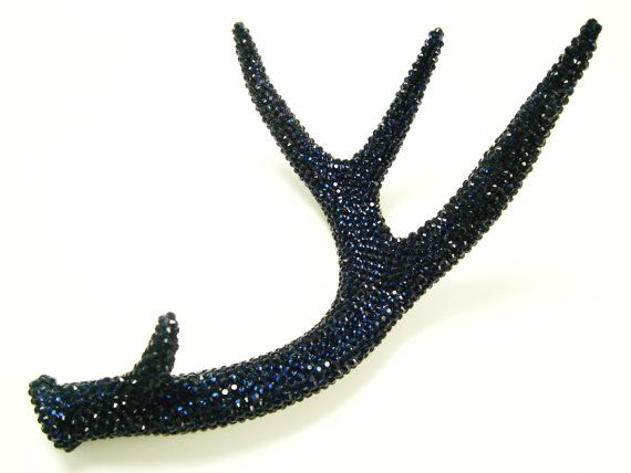 This is a naturally shed, deer antler that has been meticulously covered with 1000s of brilliant of Montana Blue crystal rhinestones. This
