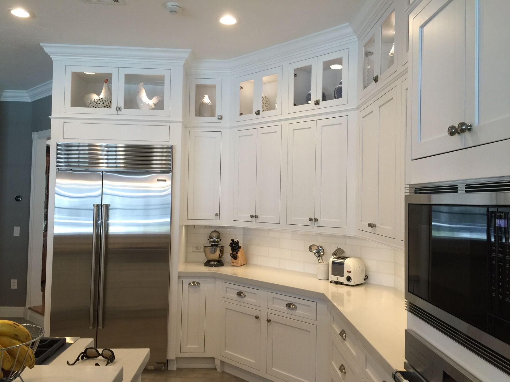 Carolyn Burrell of Today's Builders took a small kitchen in Sarasota, Florida, and turned it into a spacious space. She specified Fieldstone Cabinetry's Delhi inset door style in Maple finished in White. Modern touches include a large stainless steel range and matching wire pendant lights over the island. Additional accents include glass front cabinet doors, tapered feet on the sink cabinet and corbels on the island. Today's Builders is a Fieldstone Cabinetry dealer in Sarasota, Florida.