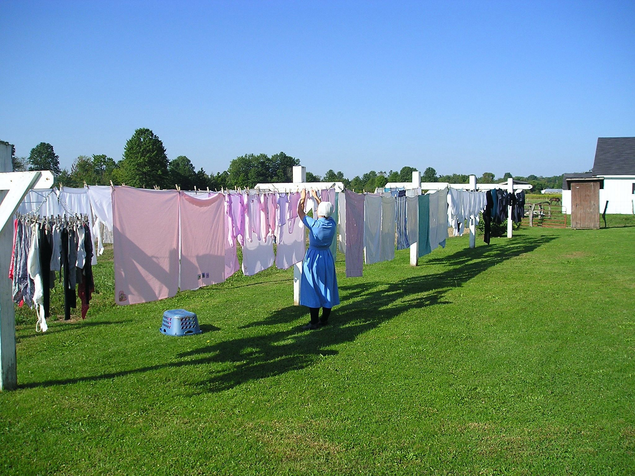 Here's a beautiful picture of an #Amish woman hanging the laundry ...