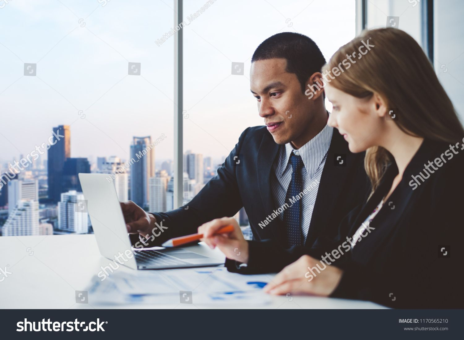 Business people discussing while meeting in office working with laptop