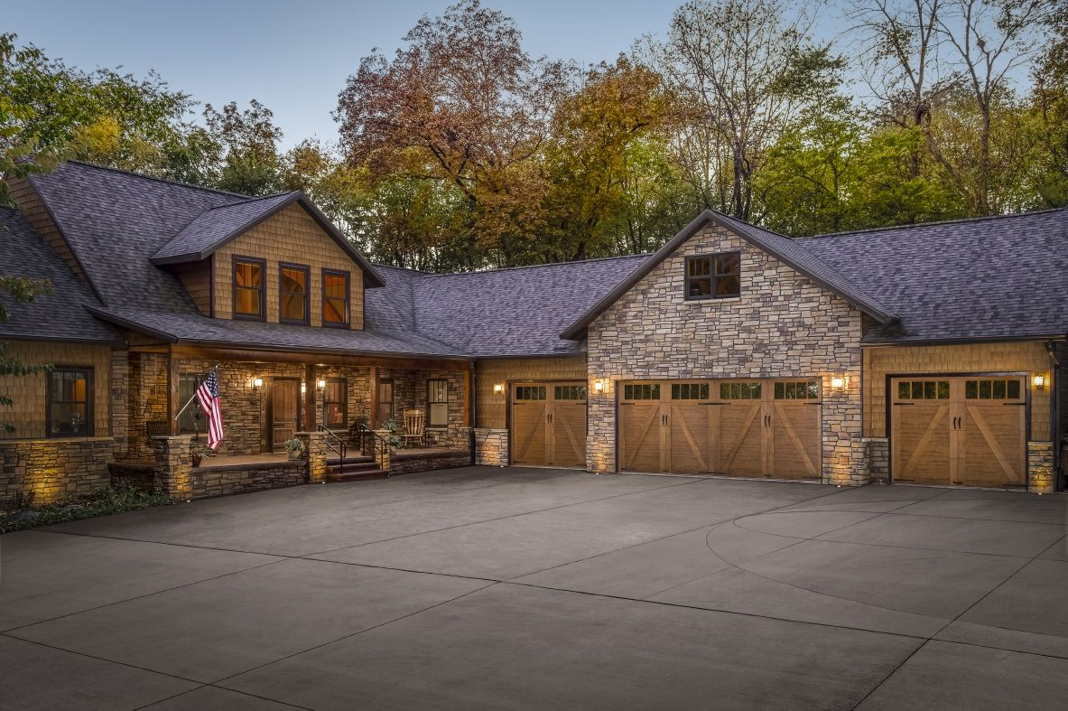 A Rustic Low Maintenance Wood Exterior With Shake Shingles Stone And Clopay Canyon Ridge Collection Ultra Faux Wood Garage Door Garage Door Makeover Shingling