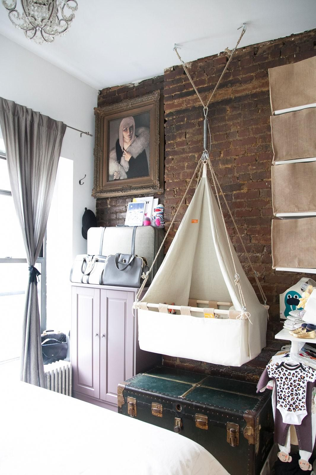 And this hanging bassinet suspended over a storage boosting antique trunk is just one genius space saving idea in this nyc couples stylish if small