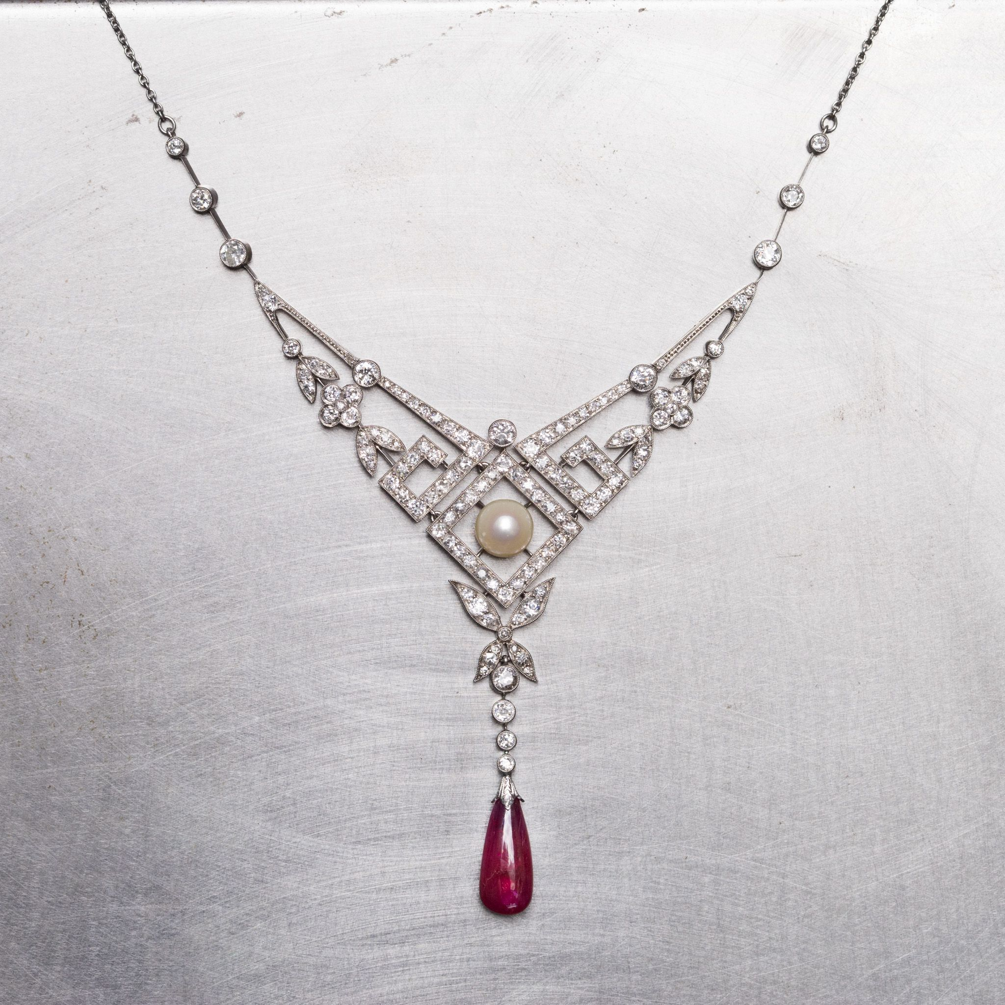Old cut diamonds. A gorgeous pearl. A drop Burma no heat ruby. All set in a piece that melds elements of nature with geometric patterns. We love everything about this Edwardian necklace.