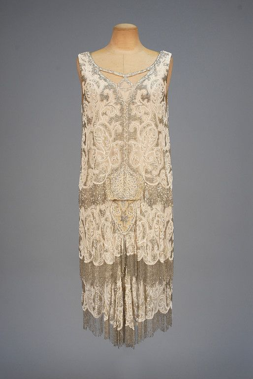 BEADED and FRINGED FLAPPER DRESS, 1920s. Sleeveless cream silk chiffon having cutout neckline decorated with pearls, rhinestones, white and crystal beads, bodice and tiered skirt fringed in crystal beads, chiffon under-dress with lace hem band. Whitaker Auctions, Fall 2015. CLICk to enlarge