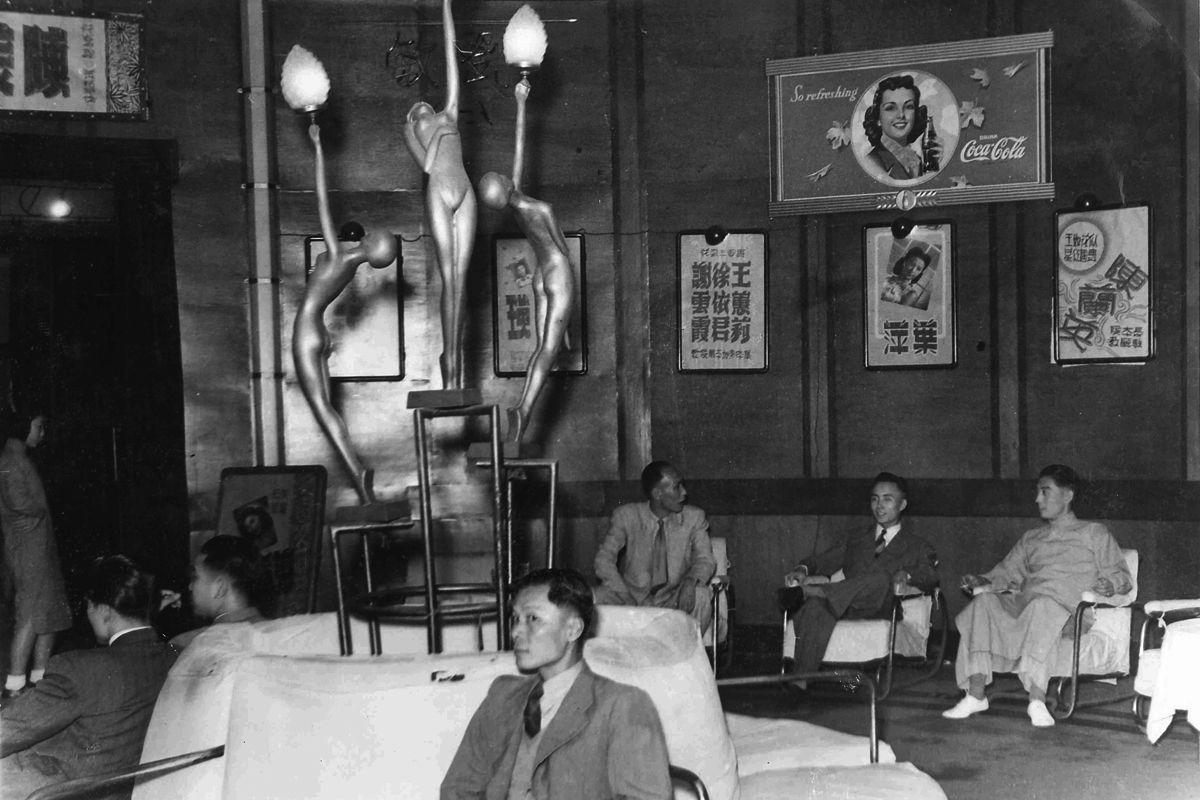 Junge Männer unter Jugendstil-Lampen  Coca-Cola Werbung in einem Theater