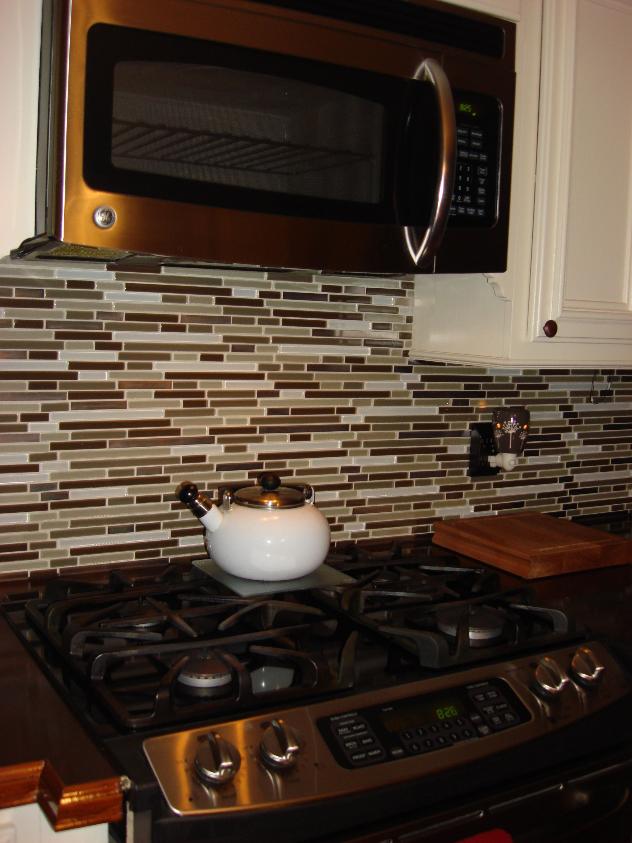 glass tile backsplash all the way up under the microwave kitchen