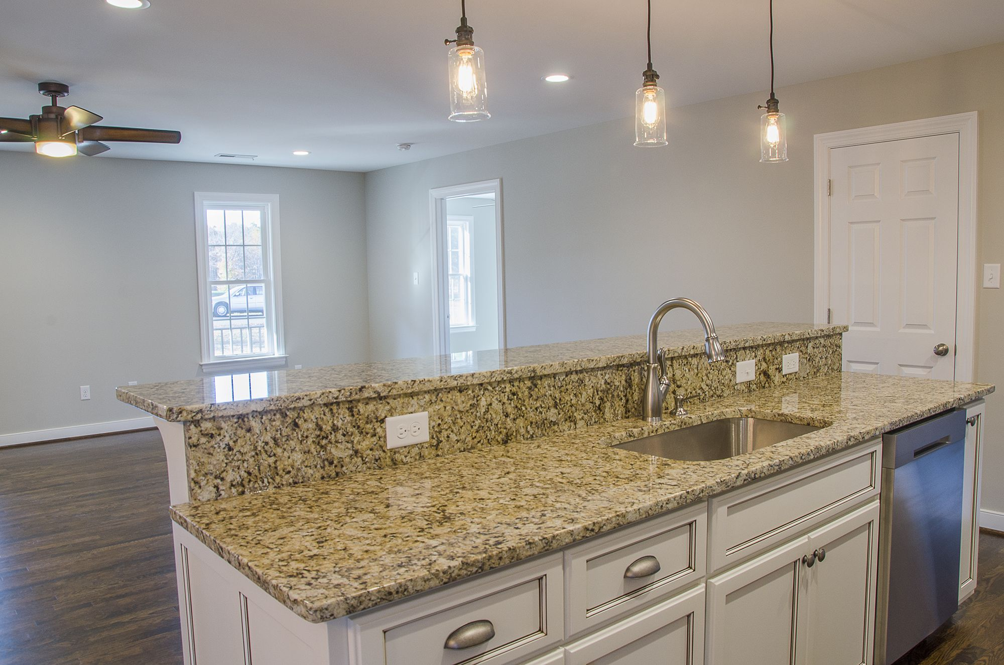 Large Kitchen Island With Granite Countertops And Farmhouse Style Cabinets The Island Features A Trio O Best Home Builders Large Kitchen Island Home Builders