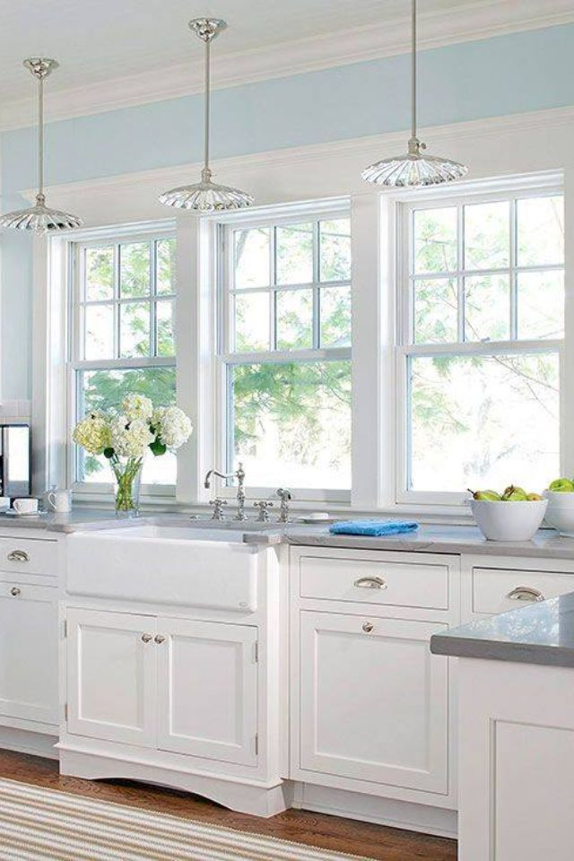 white kitchen with huge windows and pretty pendant lights