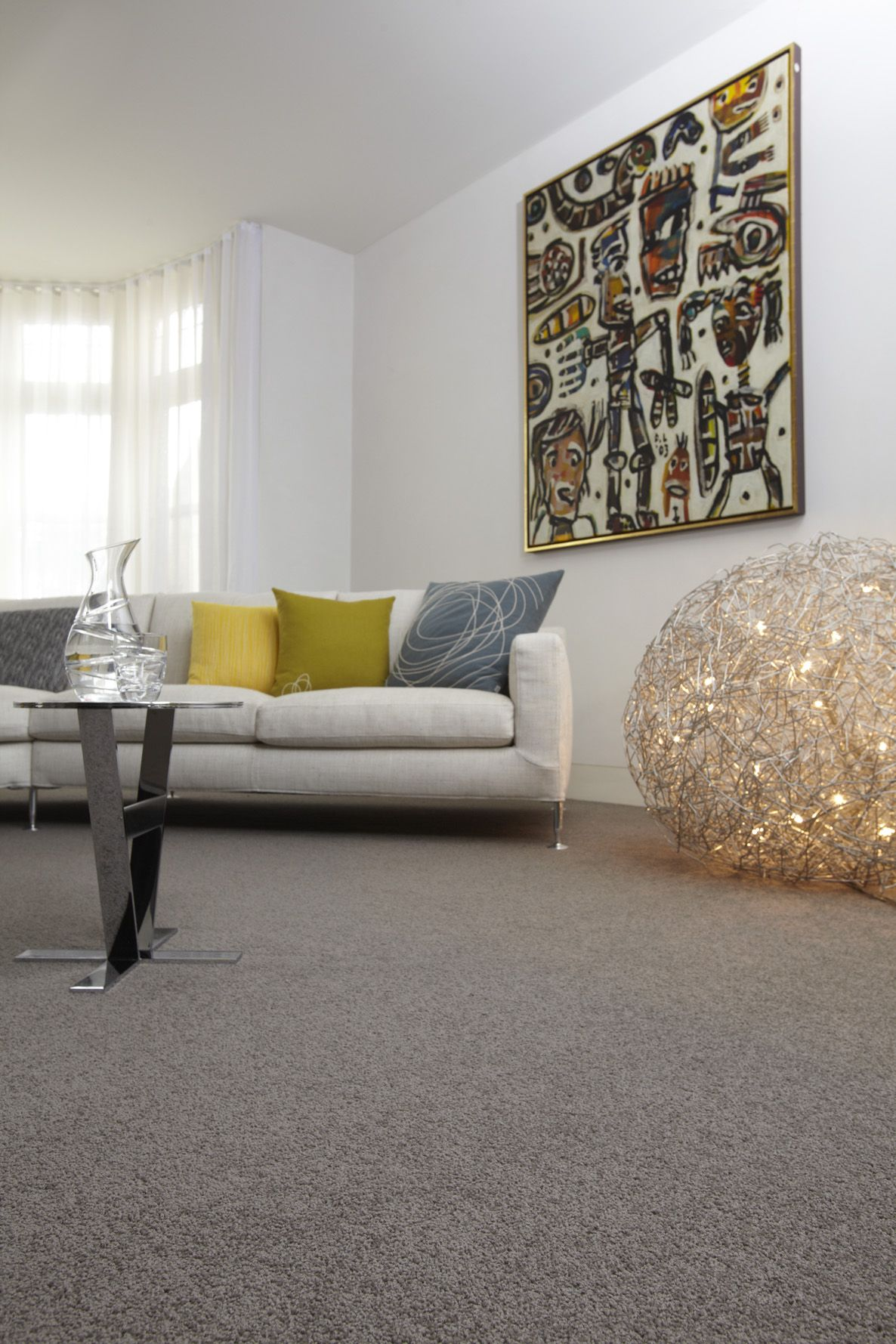 grey wool carpet creates a good base for bright accessories in this
