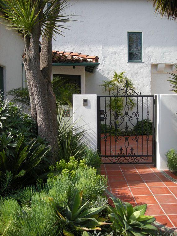 simple white stucco wall black wrought iron gate