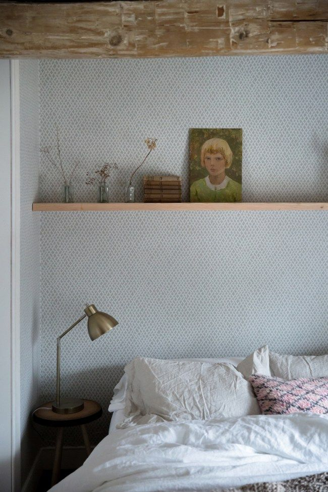 bedroom with shelf above bed art books