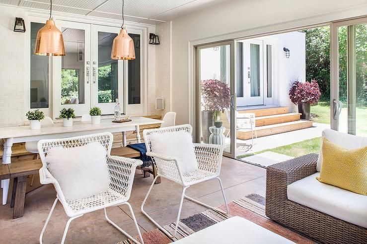 Steps Down To Sunroom Features A White Spindle Dining Table Lined With Eames Molded Plastic Chairs As Well Reclaimed Wood Bench Illuminated By
