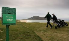 Golfers walk past the Honesty Box at the Isle of Harris Golf Club