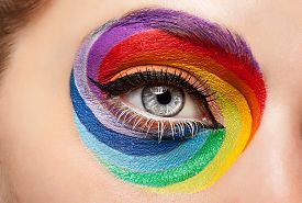 Close up eye with fashion art on stage make up. Fashion make up and excentric glamour concept. Rainbow make up pic.