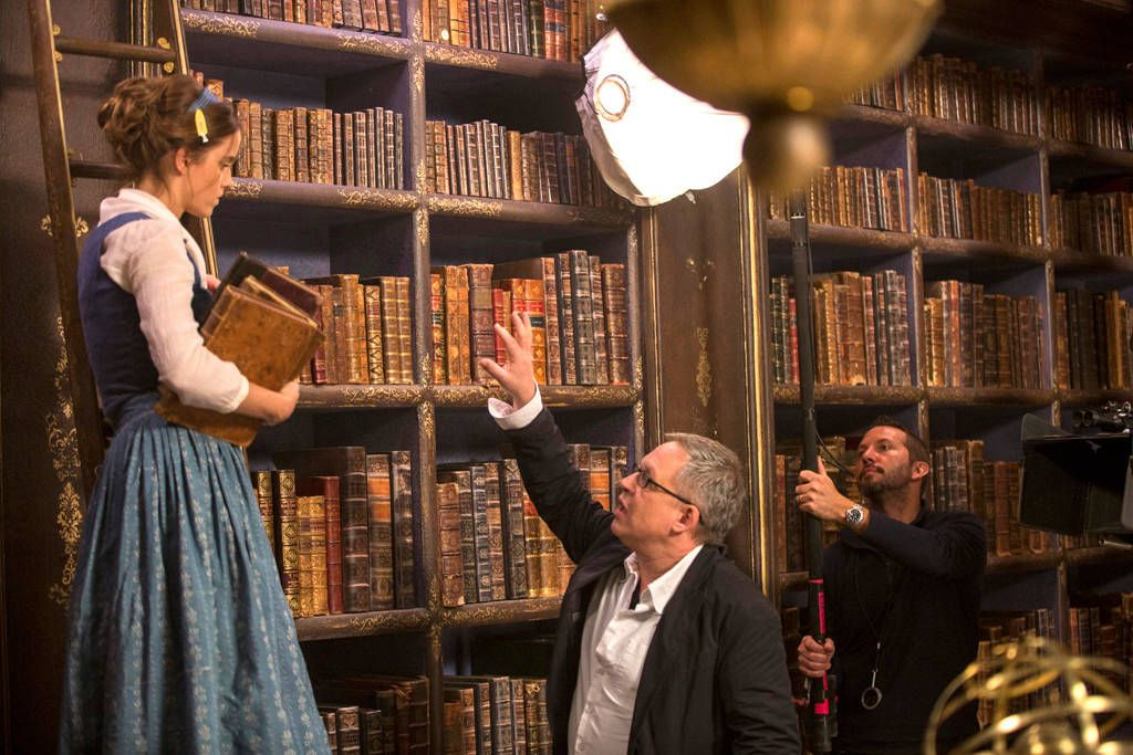 Perfecting the Shot from Beauty and the Beast Movie Stills  Stone is seen taking direction while standing in the library.