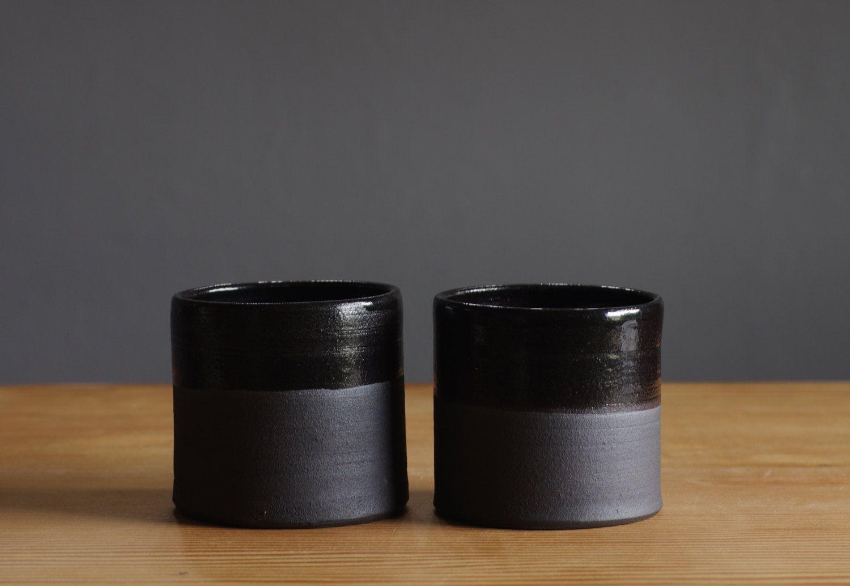 black cup pair stoneware with black glaze rustic modern dishes pottery. minimalist ceramics. $50,00, via Etsy.