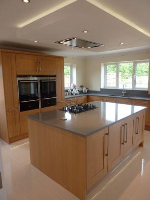 suspended ceiling with lights and flat extractor hood over kitchen