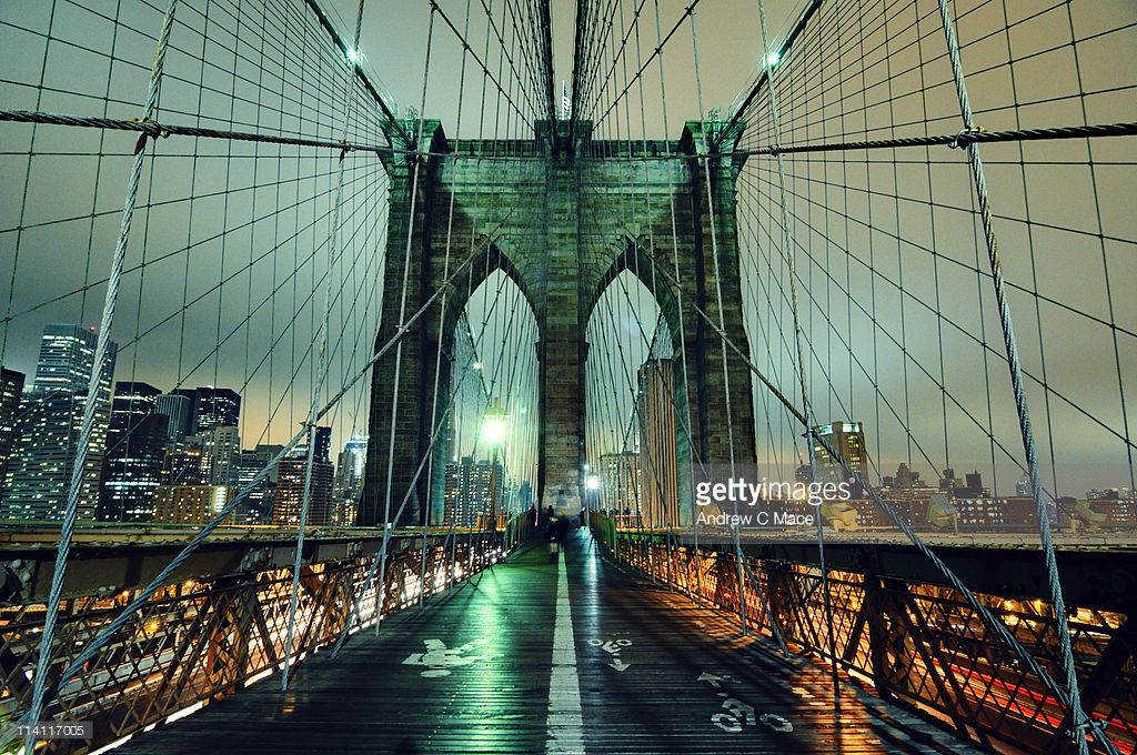 Long exposure wide angle view from the Brooklyn Bridge walkway on a cloudy night facing lower Manhattan.