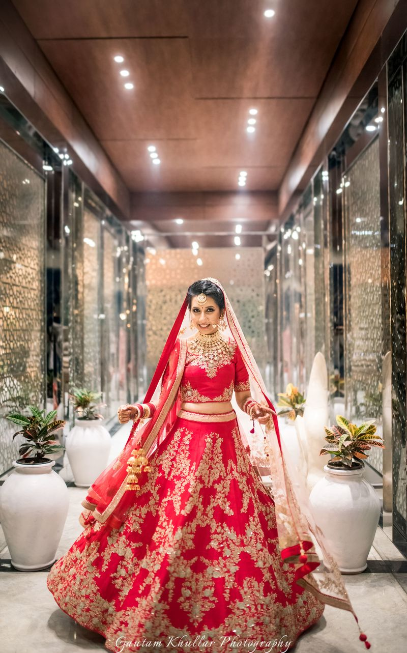 Red and gold bridal lehenga with zardozi work , twirling bride , red ...