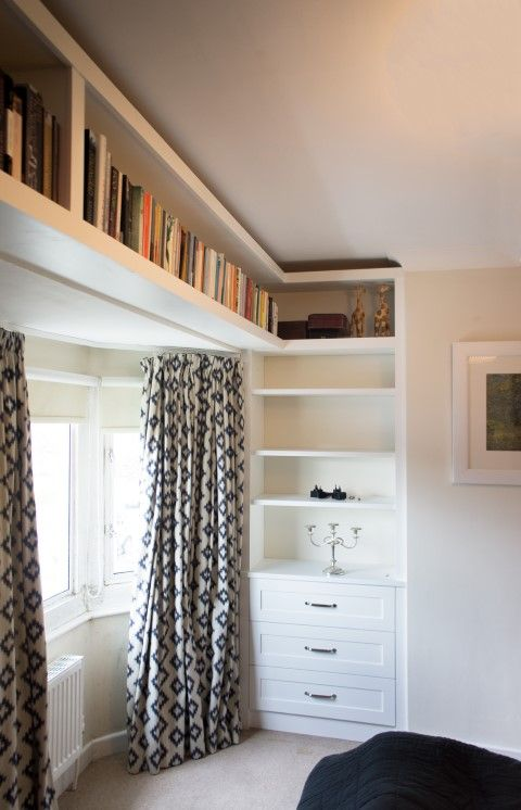 These alcove cabinets we created have a high bookcase which extends over the window bay ina small bedroom creating a real feature.