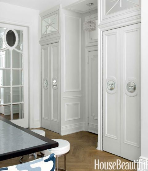 "To give presence to a standard entry door and separate it from the kitchen, Giesen created a ""foyer"" by framing the door with closets and a transom all dressed up with mirrors and molding. Finessing another awkward link, the mirrored sliding door at left shields the bathroom. Walls are in Benjamin Moore's gray-ish Paper White with White trim."