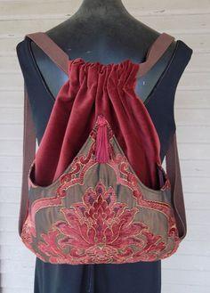 Original handmade Rucksack mit dunklen Rost samt gemacht. Die Außentasche ist von Schattierungen von Rost an Burgund und irisierende braun mit Gobelin Stoff Bögen in der Mitte und an der Stelle genäht. Diese Außentasche ist mit Satin ausgekleidet. Die Tasche selbst ist innen versäubert und misst 14 x 18.  Die Quaste ist Burgund.  Dieser Rucksack ist groß mit Außentasche für verstauen Ihr Wasser oder Buch. Macht es ideal für auf die gehen Mädchen.
