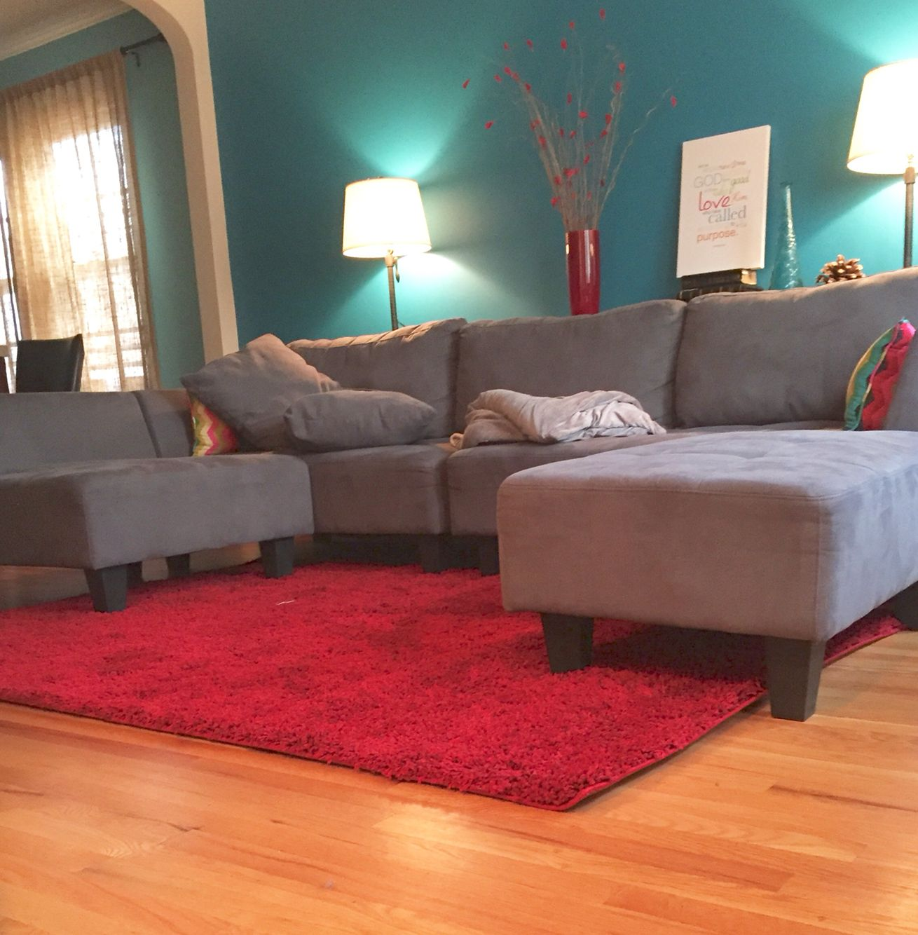 Living Room Idea: Teal Blue Wall, Grey Couch, Ruby Red Rug