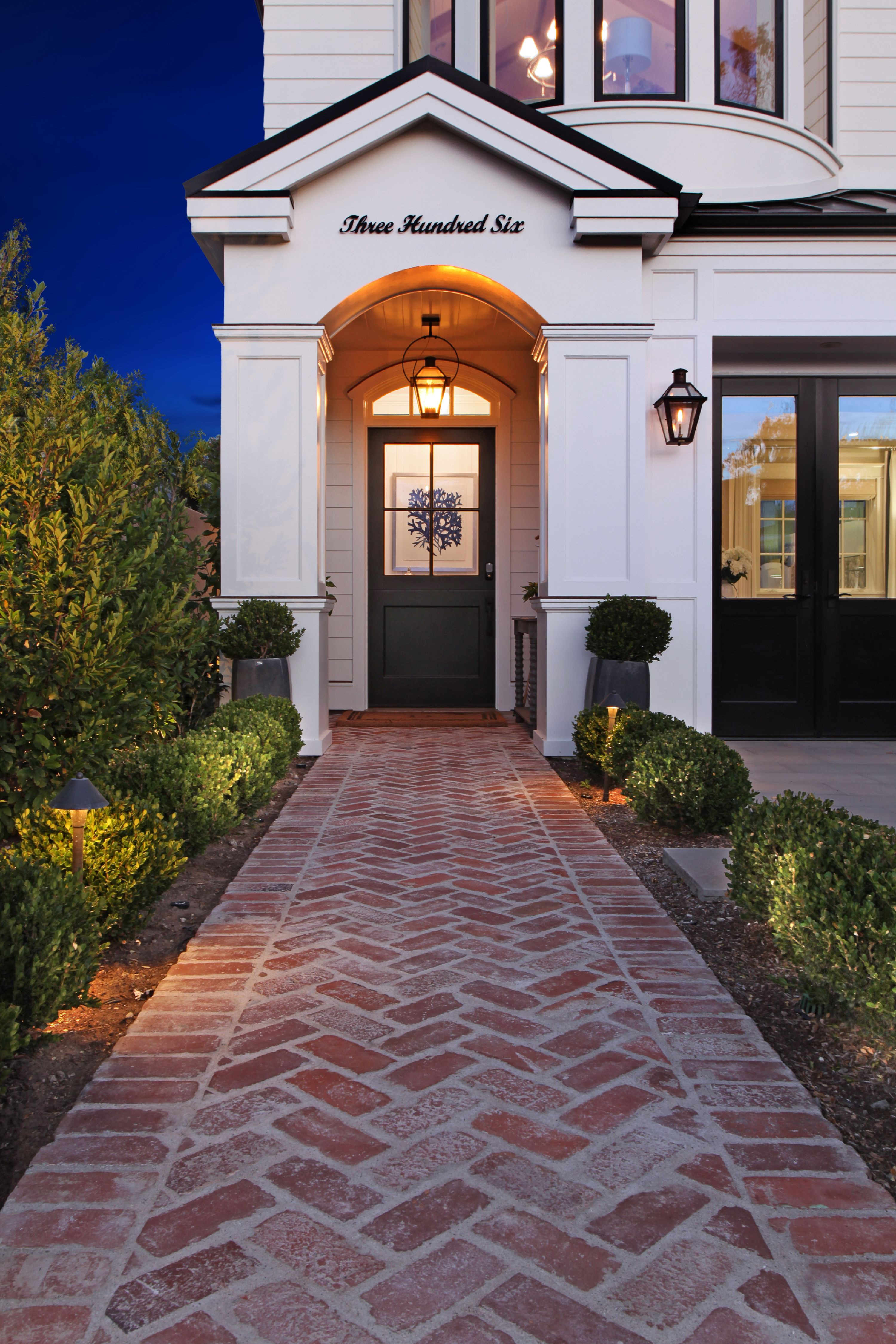 this black front door looks absolutely perfect lit up at night  we especially like the floral