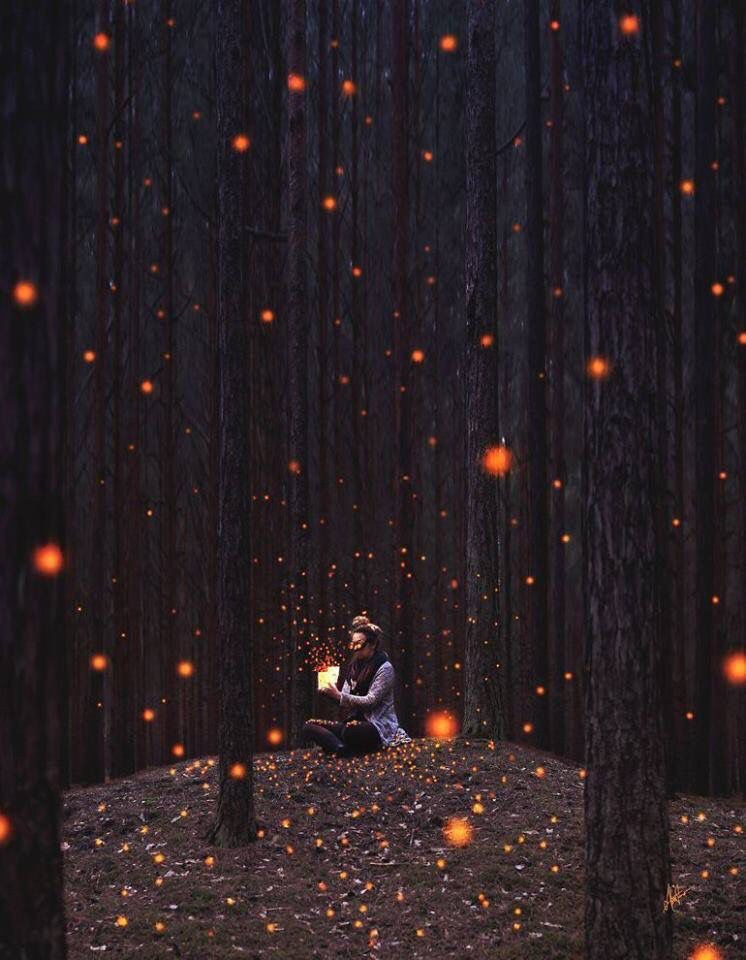 Girl wearing a mask and sitting around trees & releasing orange light