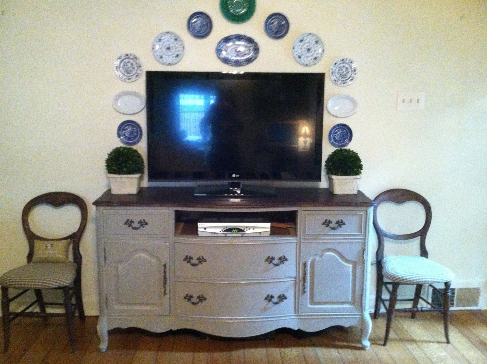 Use A Buffet As Tv Stand With Grouping Of Plates On The Wall And Flank Boxwoods Pair Antique Chairs