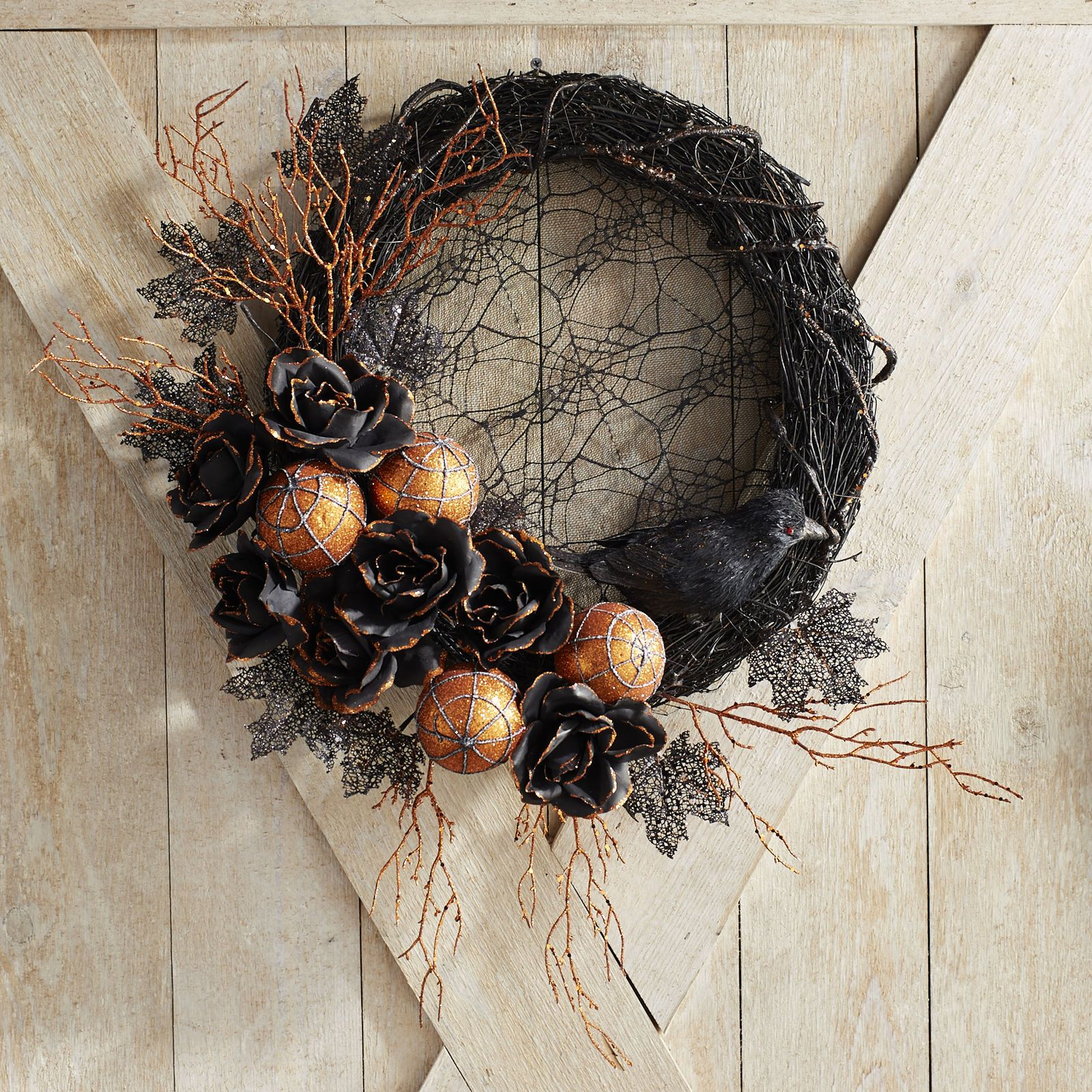 Gothic and glam are a match made in Halloween heaven. Take our black lace wreath. Its spooky yet stylish combination of cobwebs, faux florals and glittered leaves offers instant enchantment to a door or mantel. At the same time, a few bright orange accents provide a punch of seasonal color.