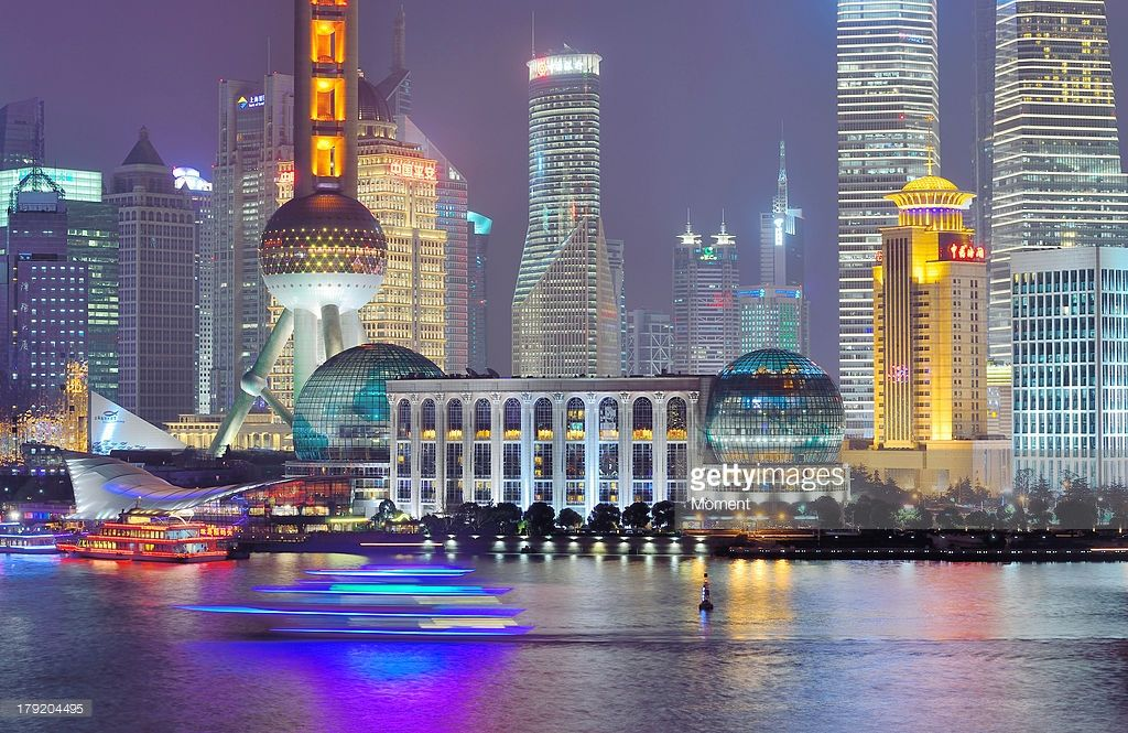 A blurred sightseeing cruise in the Huangpu River against the night skyline of Shanghai's Lujiazui Financial District.The landmark of Oriental Pearl TV Tower was lit red to celebrate the Chinese New Year of 2013.